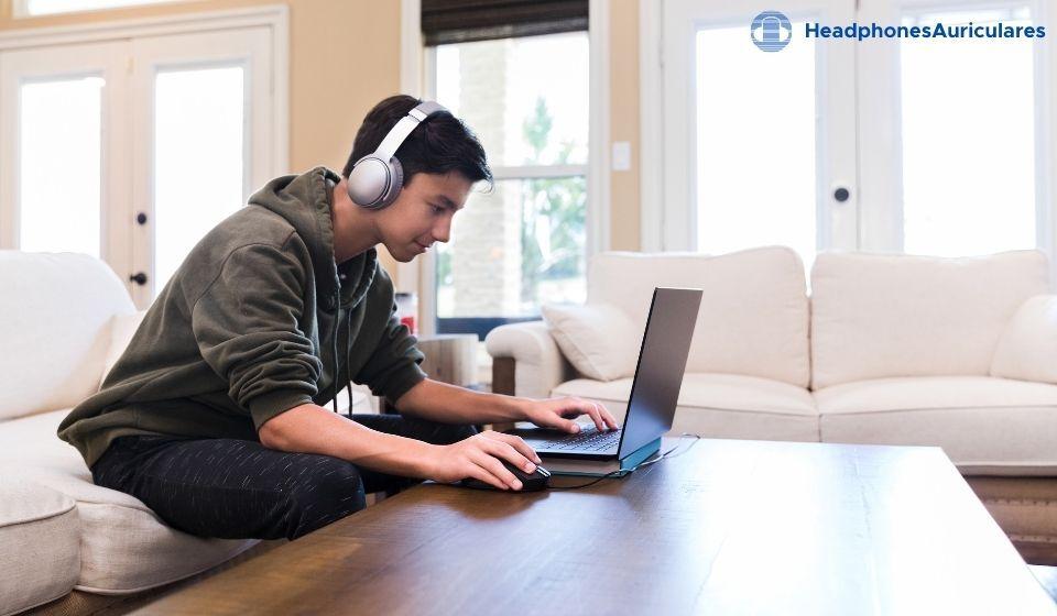 joven conectando auriculares bluetooth al computador