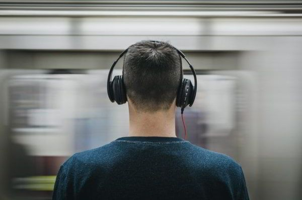 hombre con auriculares que cancelan el ruido en el metro